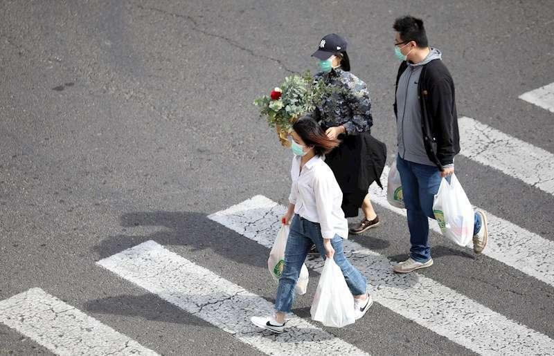 Tres personas con mascarilla y bolsas de la compra. EFE
