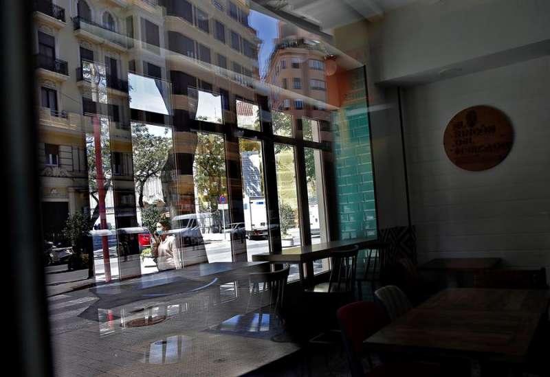 Una joven pasa ante una cafetería cerrada en el barrio del Carmen de València, en una imagen reciente. EFE