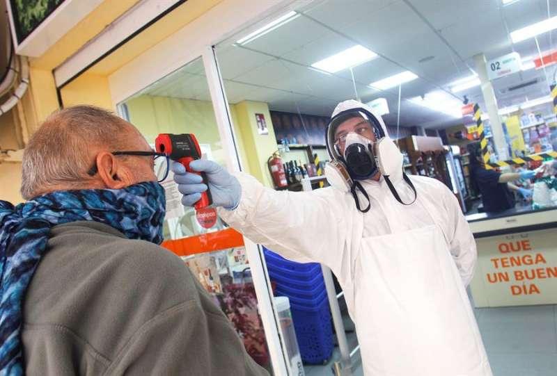 Un empleado de un supermercado de la zona de La Mata de Torrevieja toma la temperatura a sus clientes para prevenir que gente infectada acceda a la tienda y pueda contaminar productos y clientela. EFE/MORELL