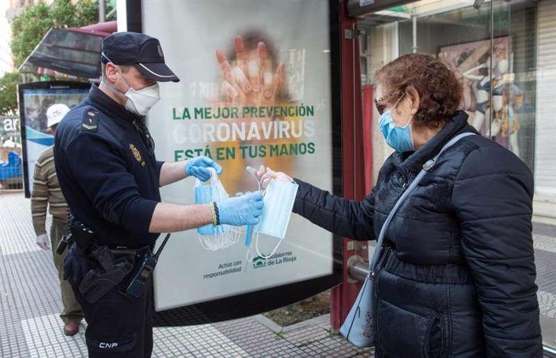 Un agente de la Policía Nacional reparte mascarillas junto a una parada de autobús. EFE/Archivo
