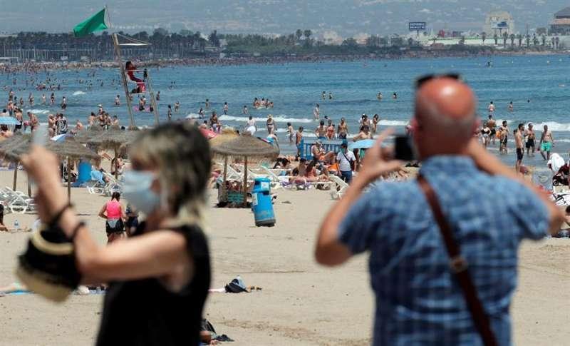 Dos personas toman fotos en una playa, protegidos con mascarillas. EFE