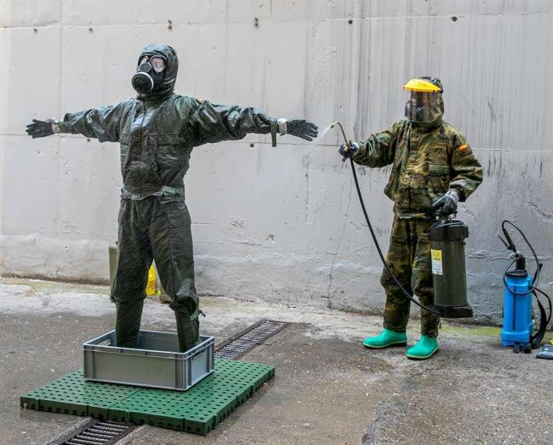 Militares de la compañía NBQ limpian sus Equipos de Protección Individual tras desinfectar una residencia de la tercera edad estos días de pandemia. EFE
