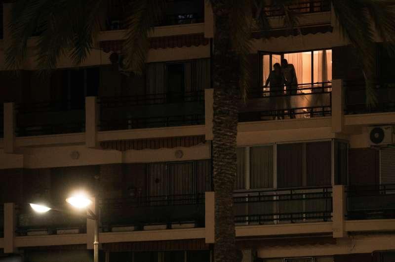 Dos personas se asoman a su balcón durante la medianoche del sábado a falta de unos días para que finalice la vigencia del estado de alarma, el 9 de mayo.