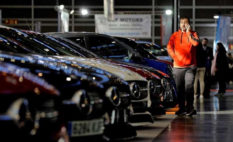 Un hombre camina ante varios vehículos expuestos en la Feria del Automóvil, en una edición anterior. - EFE