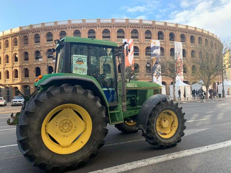 Tractor amarillo pasando por delante de la plaza de toros. EPDA