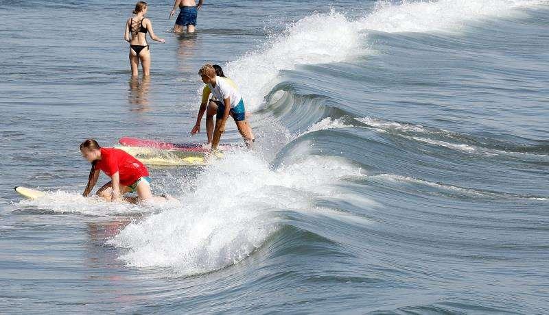 Un grupo de jóvenes practica con las tablas en la playa de la Malvarrosa de València con la resaca de las olas tras el temporal marítimo que cerró 8 playas en el término municipal. EFE/ Juan Carlos Cárdenas