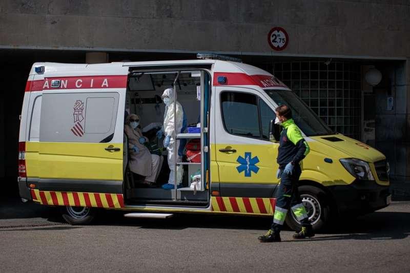 Un sanitario con un equipo de protección integral (EPI) traslada en ambulancia a un paciente al Hospital Clínico de València. EFE/Biel Aliño