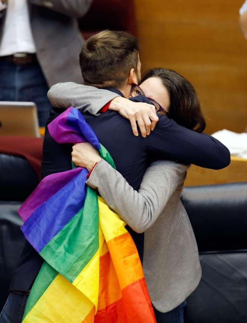 La vicepresidenta del Consell y consellera de Igualdad y Políticas Inclusivas, Mónica Oltra, abraza al portavoz de Compromís, Fran Ferri, en el pleno de Les Corts Valencianes que ha aprobado este miércoles la ley de igualdad de las personas LGTBI. EFE