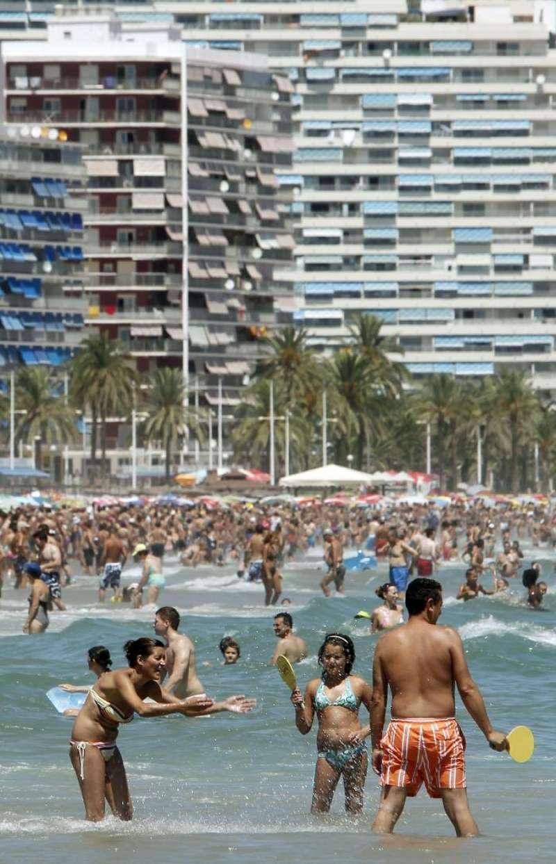 Veraneantes disfrutan al pie de los apartamentos de la playa de Cullera, en Valencia. EFE/Archivo