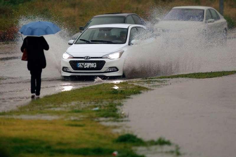 Una persona se protege de la intensa lluvia. EFE