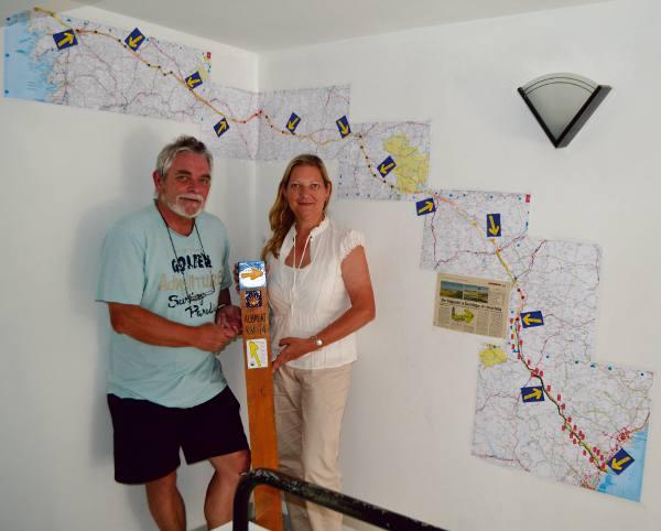La pareja de fotógrafos posa junto al mapa del camino. EPDA