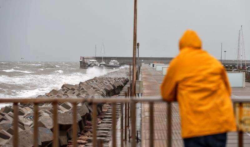 Las lluvias, el viento y los fenómenos costeros mantienen este sábado en alerta de nivel naranja, de nivel importante, a diferentes zonas de Comunitat Valenciana, Murcia y las islas Baleares. En la imagen, un hombre observa el fuerte oleaje desde el espigón de la Marina del Puerto de València. EFE