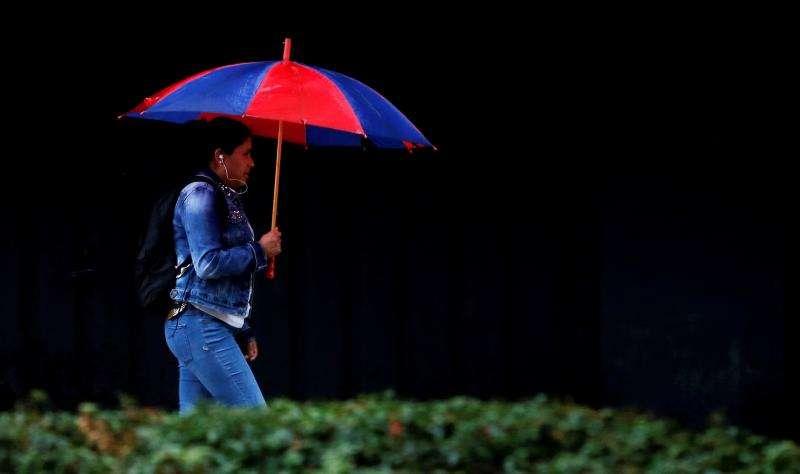 Una mujer se protege de la lluvia con paraguas. EFE/Archivo