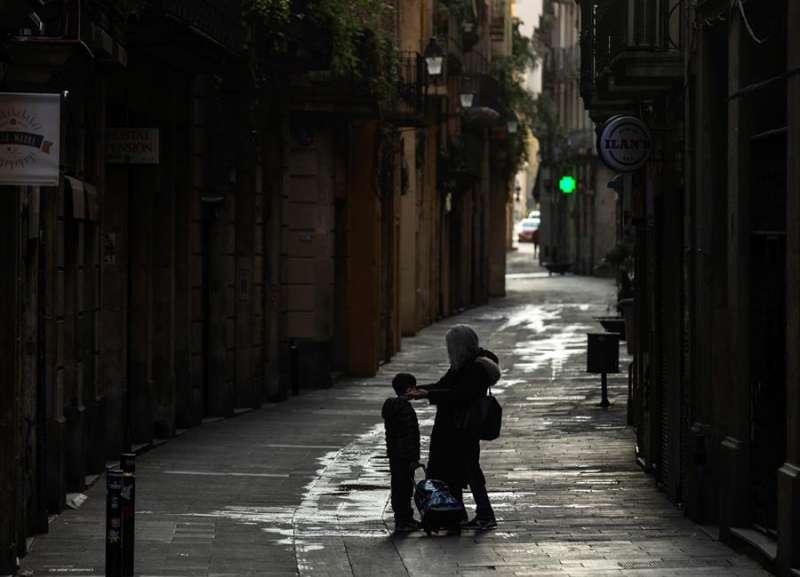 Una madre coloca la máscara a su hijo en una calle durante el estado de alarma. EFE/Enric Fontcuberta/Archivo