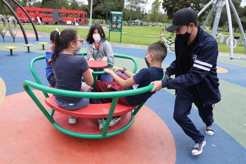 Un grupo de niños, protegidos por mascarillas, juega en el Parque Simón Bolívar de Bogotá (Colombia). EFE
