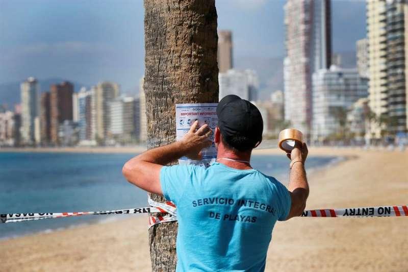 Un operario municipal coloca carteles en inglés del cierre de la playa de Benidorm.EFE/ Manuel Lorenzo