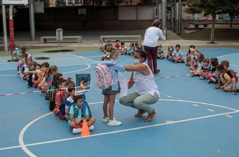 Una docente se saluda con una alumna durante el primer día de clase. EFE