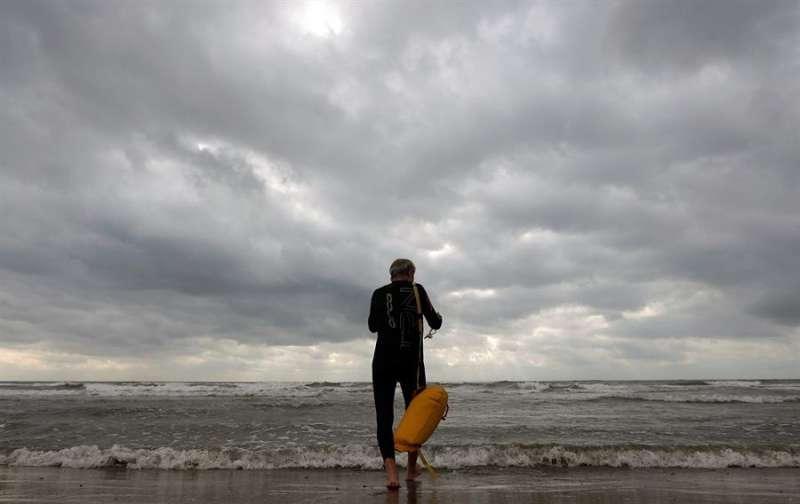 Un nadador en la playa de València, en un día nublado, en una imagen de archivo. EFE