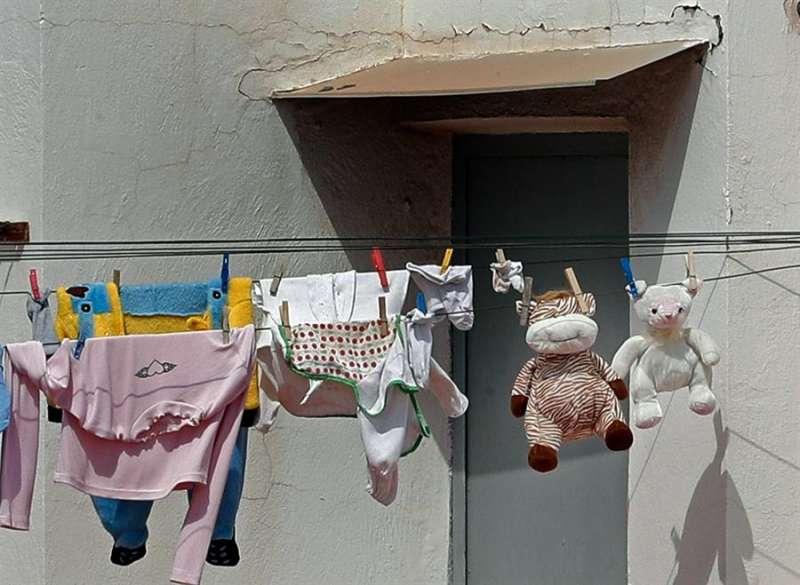 Ropa de niños junto a dos muñecos de peluche se secan al sol en una azotea de València, en una imagen de estos días. EFE/Juan Carlos Cárdenas