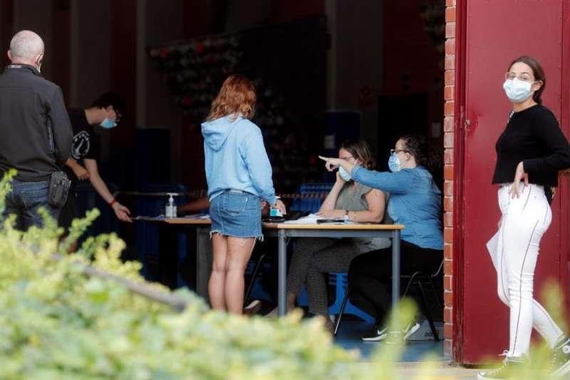Alumnos de la Universidad Politécnica de Valencia aguardan a la puerta de las instalaciones del pabellón donde se realizan pruebas PCR