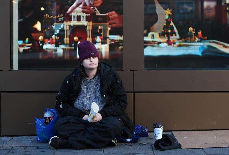 Una mujer pide dinero en una calle. EFE/Archivo