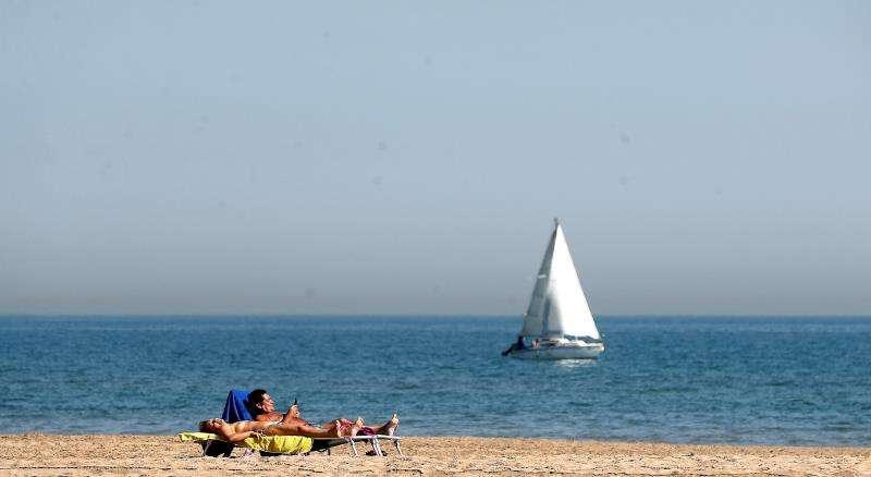 Una pareja toma el sol a orillas del mar en la playa de la Malvarrosa de València.