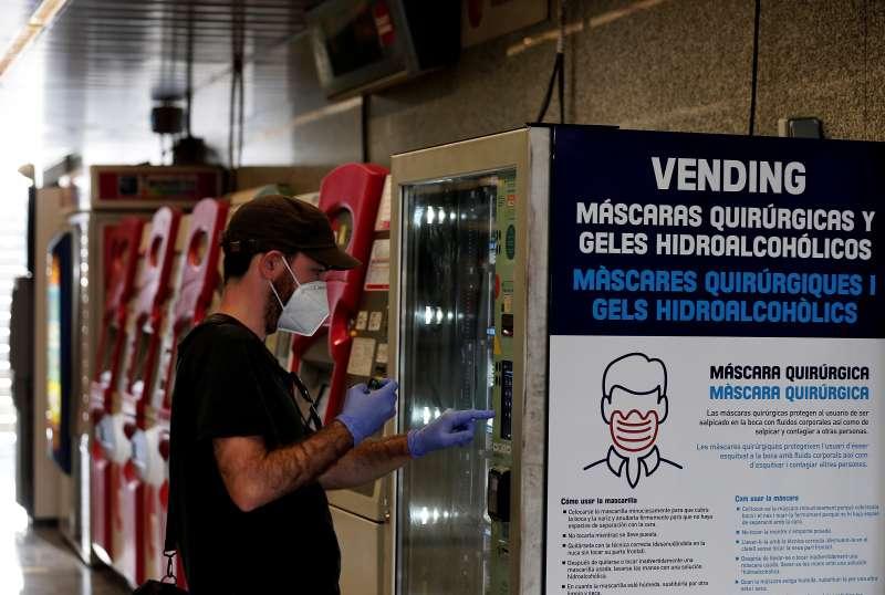 Un usuario comprando mascarillas en el metro. EFE