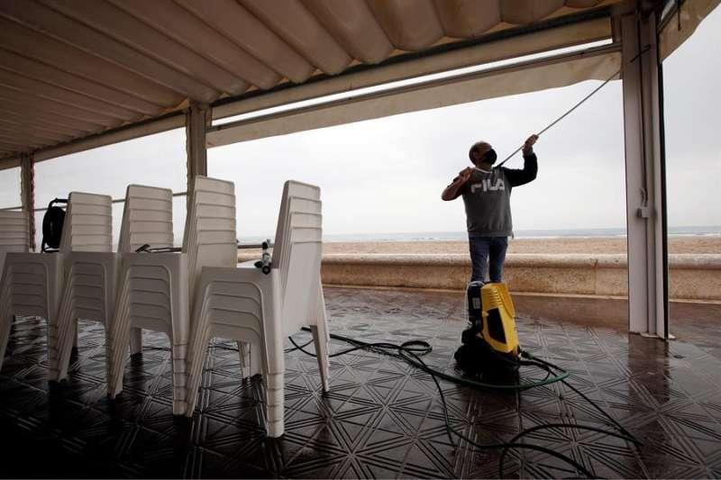 Una persona limpia una terraza de un local en el paseo marítimo de València. EFE