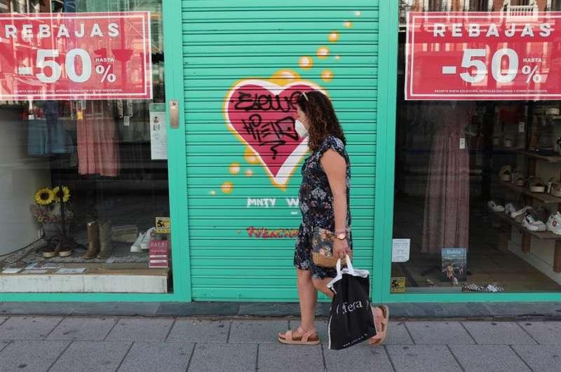 Una viandante, protegida con mascarilla, pasa por delante de una tienda de ropa. EFE/Archivo