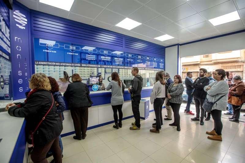 Varias personas hacen cola en una administración de lotería de Manises (Valencia). EFE/ Biel Aliño