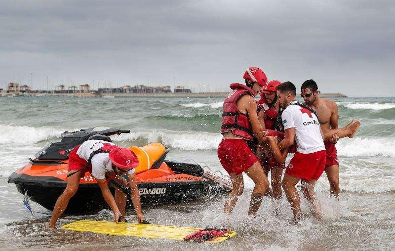 Varios socorristas intervienen durante el simulacro de rescate de un bañista en la playa de Pinedo de València. EFE