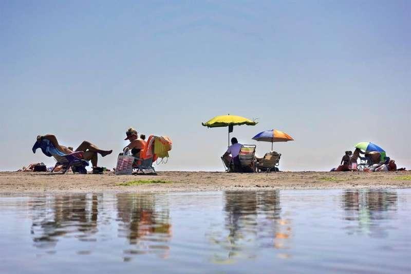 Varías personas disfrutan de la playa de La Patacona de Alboraia. EFE/Manuel Bruque/Archivo