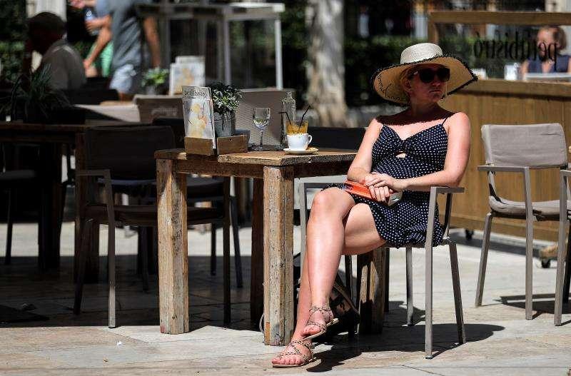 Durante la pasada madrugada se han registrado temperaturas mínimas excepcionalmente altas, por encima de los 20 grados, por segunda jornada consecutiva en varios puntos del litoral sur de Valencia y norte de Alicante. Una turista toma un café, este viernes al mediodía en la céntrica plaza de la Virgen de Valéncia. EFE