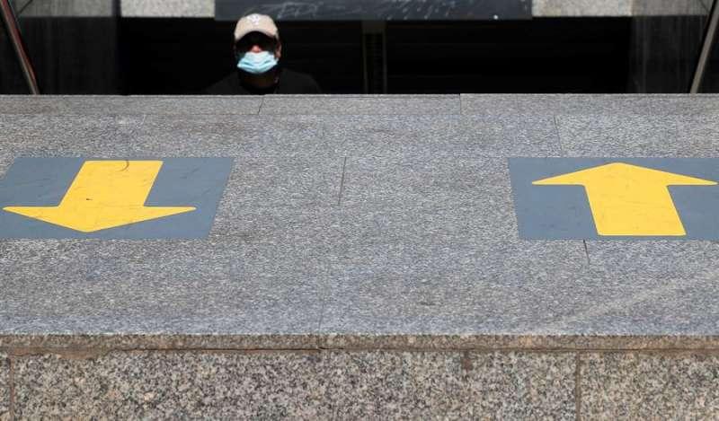 Una persona con mascarilla sale de una boca del metro en la que está señalizado el sentido de tránsito en esta