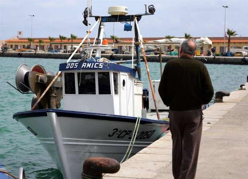 Una persona observa un barco en el puerto de Benicarló. EFE