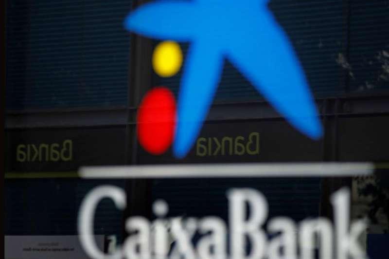 Vista de una oficina de CaixaBank y otra de Bankia reflejada en el cristal en el centro de L