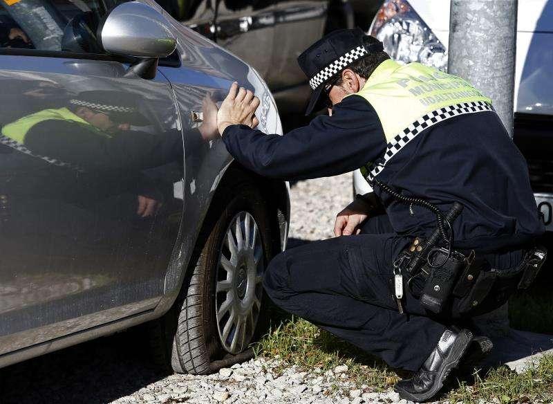 Un agente municipal observa la rueda de un vehículo pinchada. EFE/Archivo