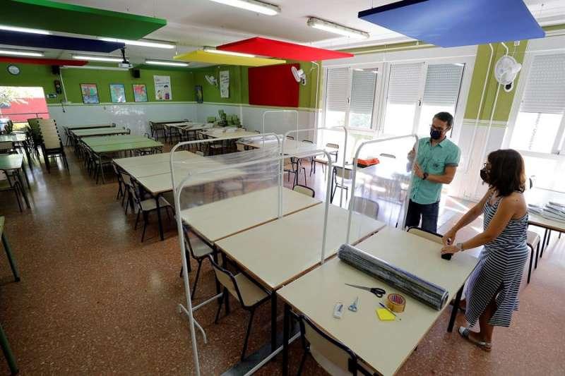 Xavi Leal y Carolina Ramos, director y jefa de estudios, respectivamente, del CEIP Jaume I de Catarroja, colocan los parabanes en las aulas. EFE