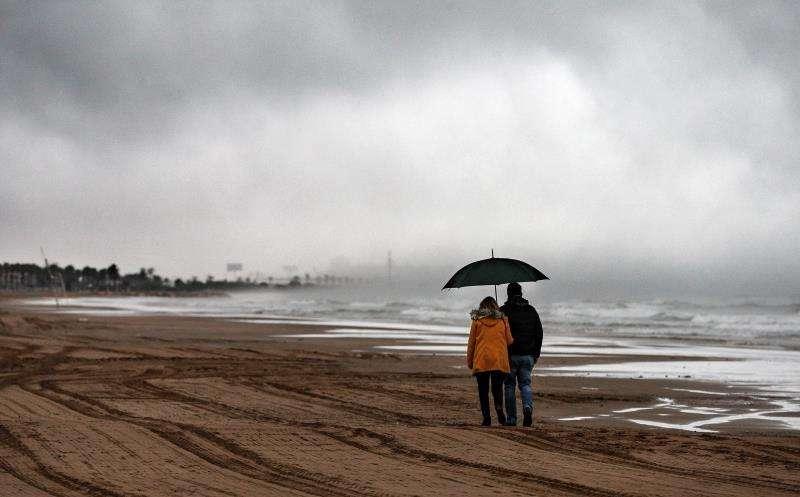 Una pareja pasea bajo la lluvia por la playa de la Malvarrosa de València. EFE/Archivo