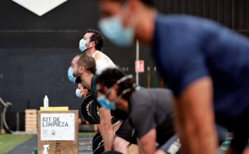 Varias personas, todas con mascarilla, entrenan en un gimnasio recién reabierto. EFE