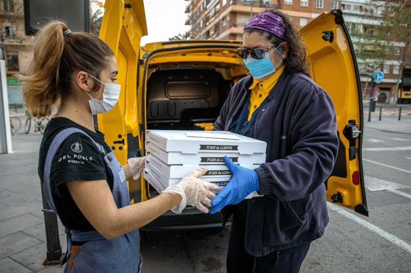 La empleada de la pizzería Del Poble Itziar Úbeda, entrega a una voluntaria de Correos las pizzas realizadas para Food4heroes. EFE