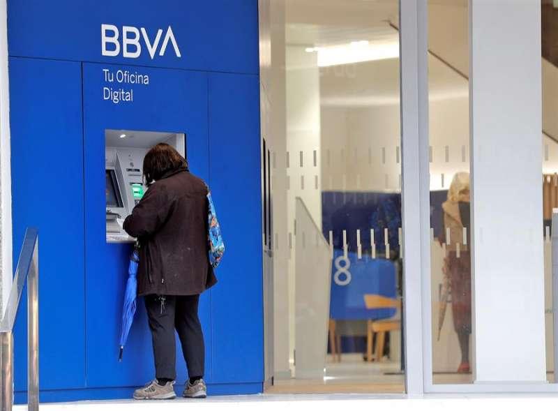 Una persona realiza una gestión en el cajero de un banco. EFE