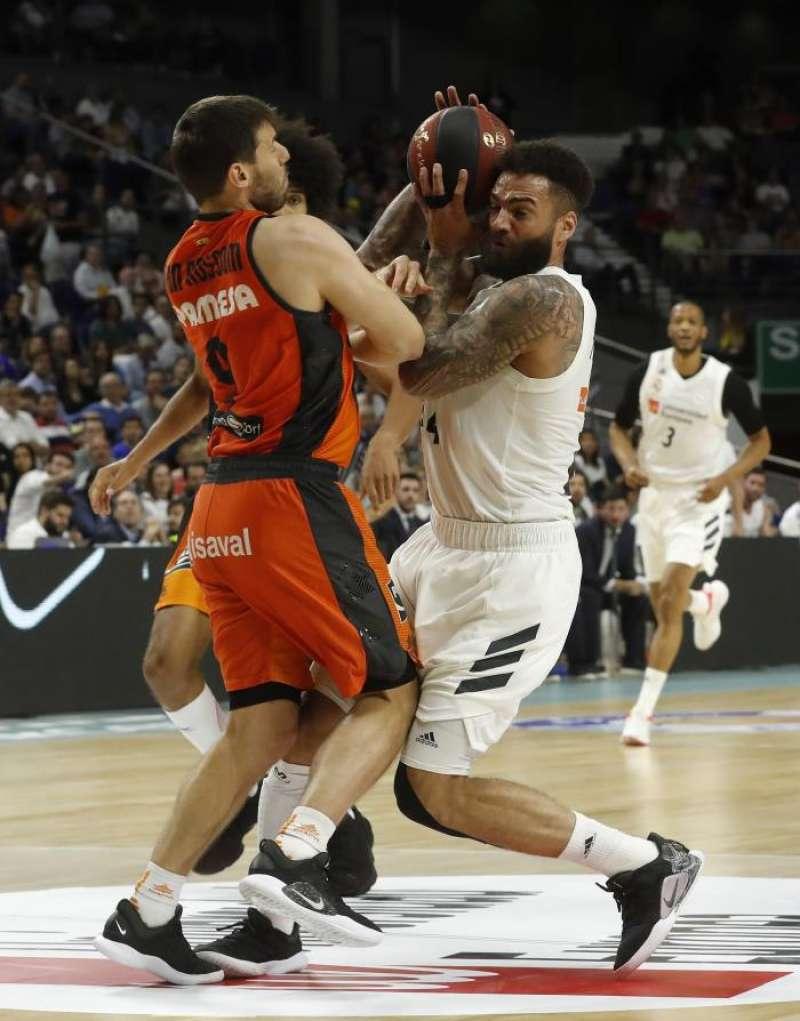 El pivot caboverdiano del Real Madrid, Walter Tavares (d), machaca la canasta ante el alero de Valencia Basket, Joan Sastre, durante el segundo partido de la semifinal de los play off que disputaron en el Palacio de los Deportes de Madrid. EFE
