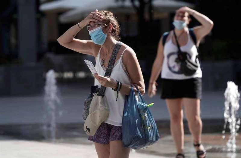 Dos personas con mascarilla por la calle, en una imagen reciente. EFE