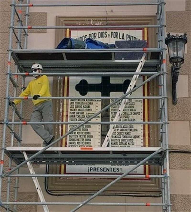 Unos operarios, este martes en un andamio ante el mural. EFE