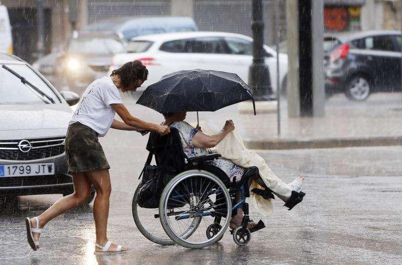 Dos personas cruzan la calle en medio de una tormenta. EFE/Archivo