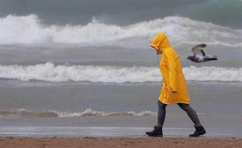 Una persona pasea por la playa de la Malvarrosa bien protegida contra la lluvia durante el temporal. EFE/Kai Försterling