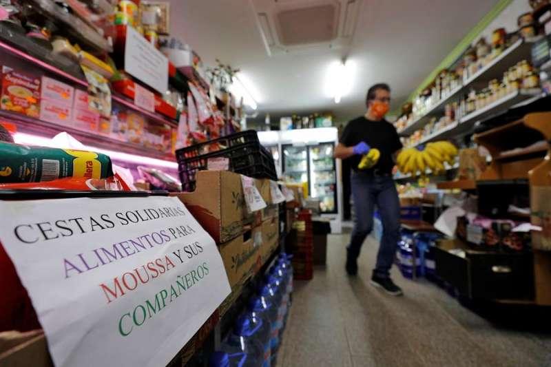 Un pequeño ultramarinos de València que abrió hace 55 años aprovecha que sigue con la persiana levantada para recaudar alimentos y dinero para cinco migrantes del barrio. EFE/Manuel Bruque