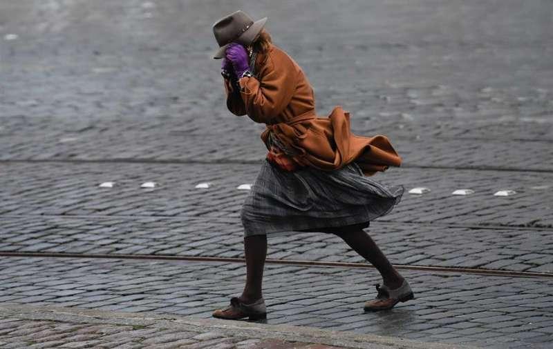 Una mujer camina contra el fuerte viento. EFE