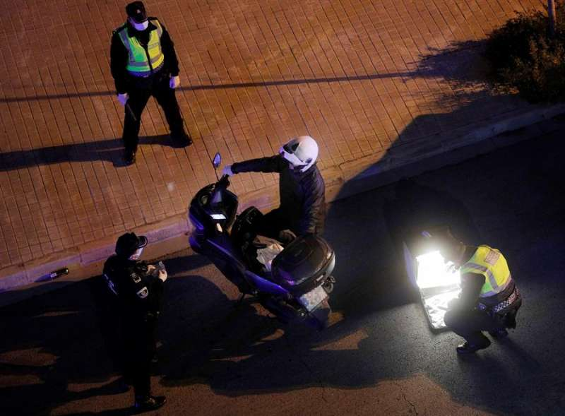Una patrulla de la Policia Local de Burjassot revisa el contenido de la mochila de un repartidor de comida en un control nocturno. EFE/Kai Försterling